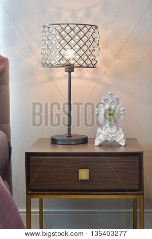 Crystal Reading Lamp And Classic Clock On Bedside Table In Cozy Bedroom Interior