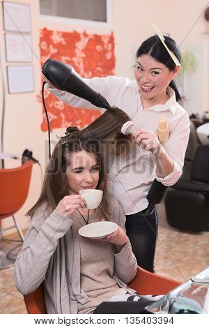 Young woman looking at camera together with hairdresser. Beautiful lady drinking coffee while having her hair washed in hairdressing salon.