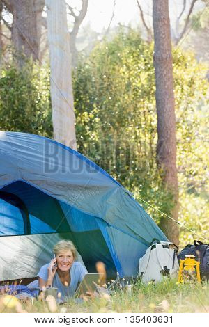 Mature woman laying and calling on the phone on campsite