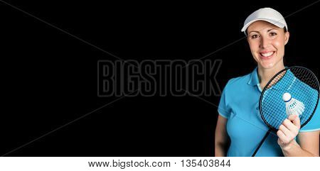 Happy badminton player holding badminton racket and shuttlecock on black background