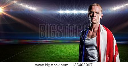 Athlete with american flag wrapped around his body against rugby stadium