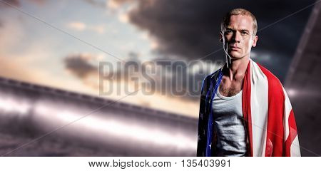 Athlete with american flag wrapped around his body against composite image of arena and cloudy sky