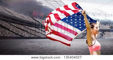 Profile view of sportswoman raising an american flag against rugby stadium