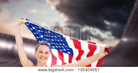 Portrait of happy sportswoman posing with an american flag against composite image of arena and cloudy sky