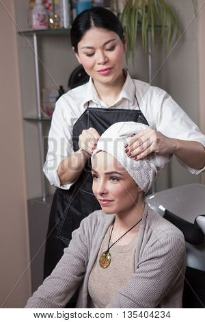 Beautiful lady sitting inchair after having her hair washed in hairdressing salon. Barber girl preparing hair for haircut.