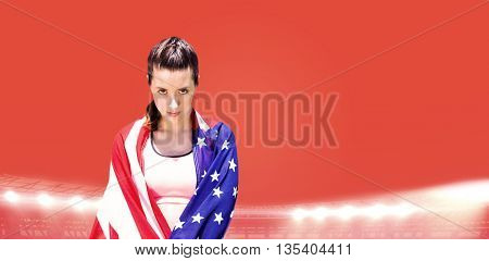 Portrait of sporty woman holding American flag against red background