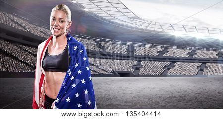Athlete with american flag wrapped around her body against rugby stadium