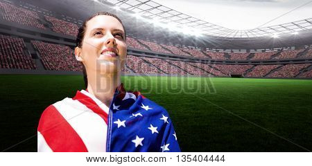 Low angle view of sporty woman holding a American flag against rugby stadium