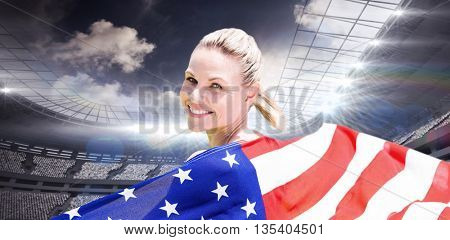 Sporty girl holding an American flag against rugby stadium