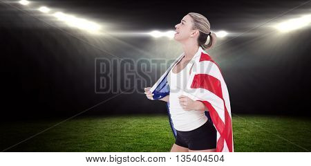 Female athlete with american flag on her shoulders against rugby stadium