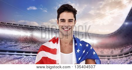 Athlete with american flag wrapped around his body against composite image of arena sport against cloudy sky
