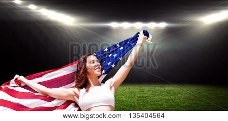 Happy sportswoman posing with an american flag against rugby stadium