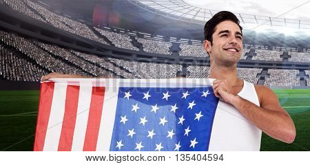 Athlete posing with american flag against rugby stadium