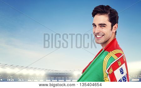 Athlete with portuguese flag wrapped around his body against large football stadium under bright blue sky