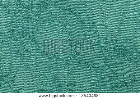 Light green pearl wavy background from a textile material. Fabric with natural texture closeup. Upholstery fabric pleated.