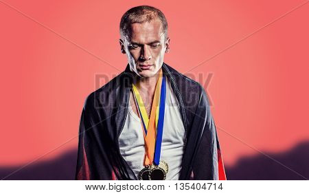 Athlete with german flag wrapped around his body against orange