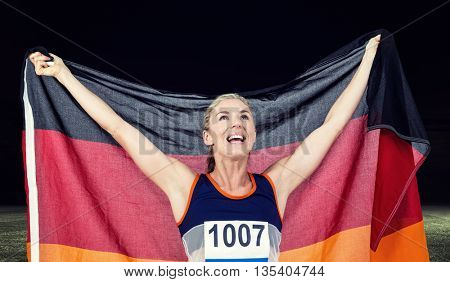 Athlete posing with german flag after victory against rugby stadium