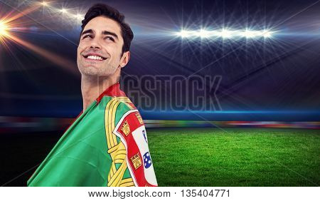 Athlete with portuguese flag wrapped around his body against rugby stadium