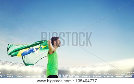 Profile view of Brazilian sportsman is holding a flag against large football stadium under bright blue sky