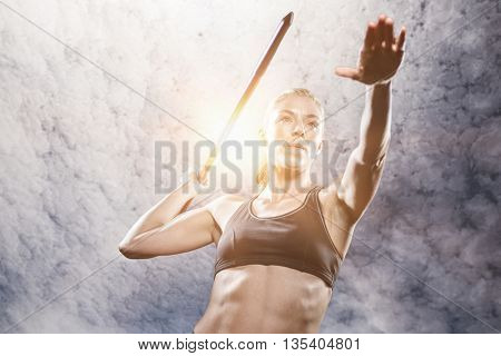 Athlete preparing to throw javelin against low angle view of sky
