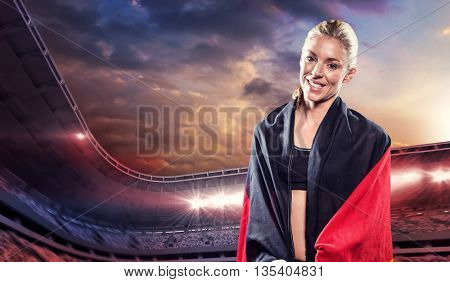 Athlete posing with german wrapped around her body against composite image of stadium with cloudy sky