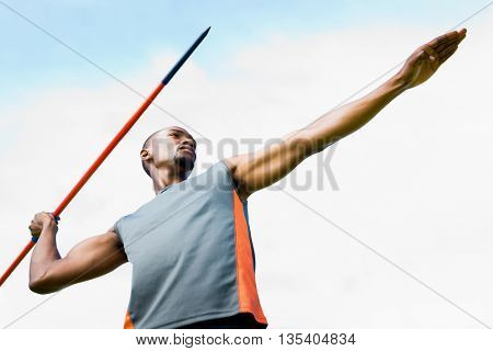 Low angle view of sportsman practising javelin throw against blue sky with clouds