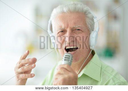 Senior man in headphones singing into microphone