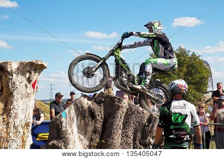 ASTON TIROLD, UK - AUGUST 8: James Dabill successfully jumps across multiple tree stumps without incurring penalties at the NBMCC Supertrial event at Seymours arena on August 8, 2015 in Aston Tirold