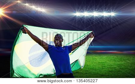 Front view of Brazilian sportsman is smiling and raising a flag against rugby stadium