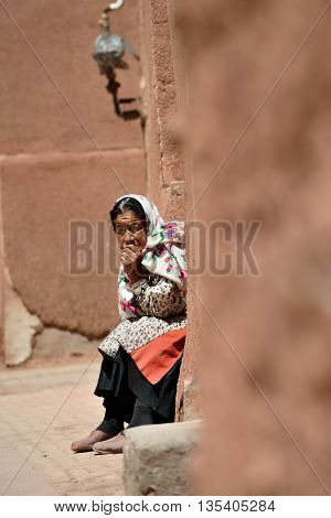 ABYANEH - APRIL 20: Unknown old woman resting in a street in Abyaneh, Iran on April 20, 2015. Abyaneh is small mountain village, at the 2006 census, its population was 305, with 160 families.
