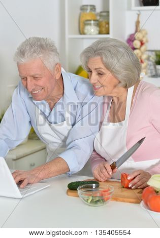 Happy senior man and woman  in the kitchen with laptop