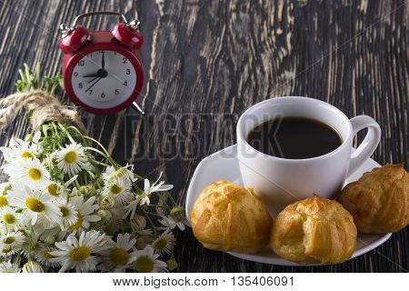 Eclair, coffee cup, alarm clock and charmomile on wooden background.