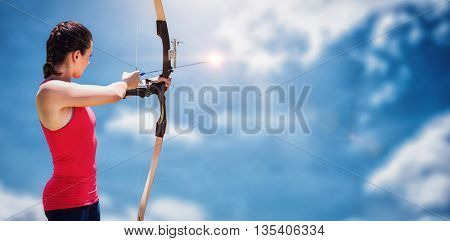 Side view of woman practicing archery against blue sky