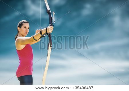 Sportswoman practicing archery on a white background against blue sky