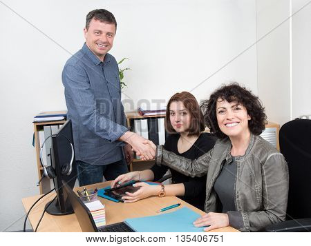 Two Businesspeople Shaking Hand In Front Of Colleague In Office