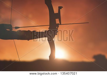 Close up of someone practising archery against landscape with sunset