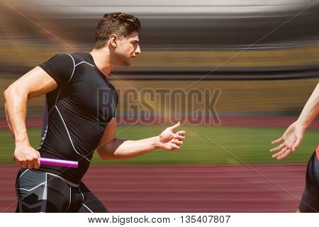 Athletic man running a relays against athletic track in a stadium