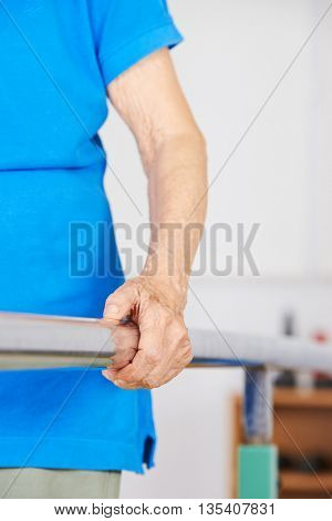 Arm and hand of old woman on horizontal bar during physiotherapy
