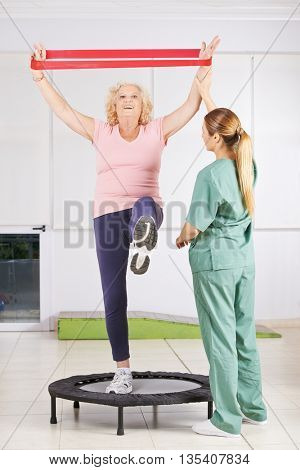 Old woman exercising with latex band in physiotherapy