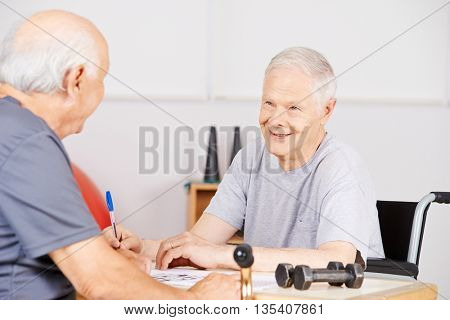 Old man in nursing home with crossword puzzle for memory training