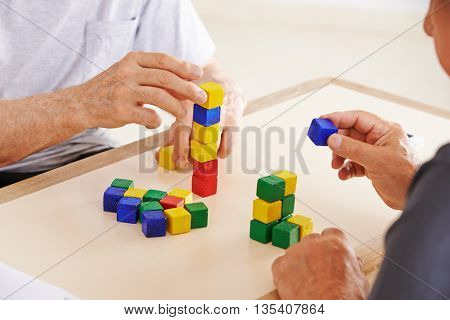 Hands of demented senior people playing with colorful building bricks