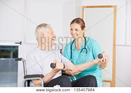 Old man in wheelchair lifting dumbbells in physiotherapy