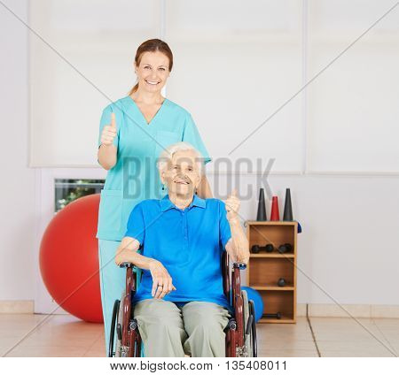 Happy old woman in wheelchair holding her thumbs up with geriatric nurse