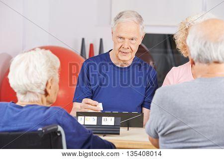 Senior people playing rummikub game together in nursing home
