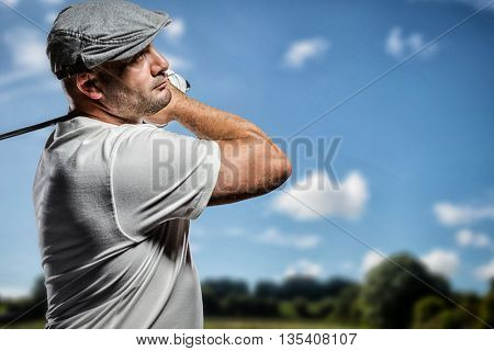 Portrait of golf player taking a shot against green field