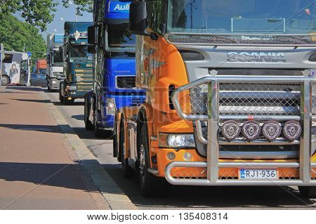 HELSINKI, FINLAND - JUNE 21, 2016: Group of Finnish truck drivers in convoy protest against the new EC Cabotage rules near the Finnish Parliament House in Helsinki.