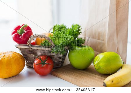 cooking, diet, vegetarian food and healthy eating concept - close up of basket with fresh ripe juicy vegetables, greens and fruits on kitchen table at home
