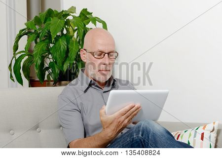 a mature man at home websurfing on internet