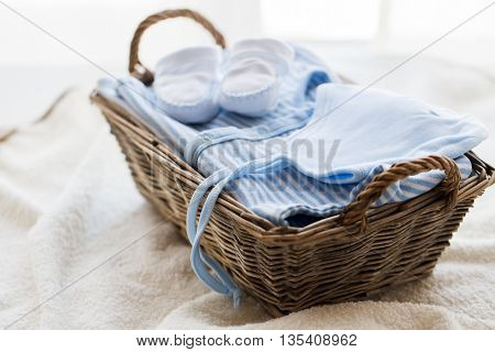 clothing, babyhood, motherhood and object concept - close up of white baby bootees with pile of clot
