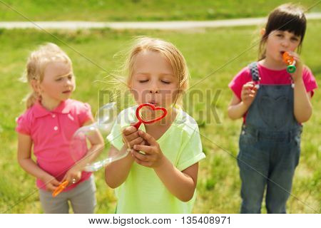 summer, childhood, leisure and people concept - group of kids blowing soap bubbles outdoors